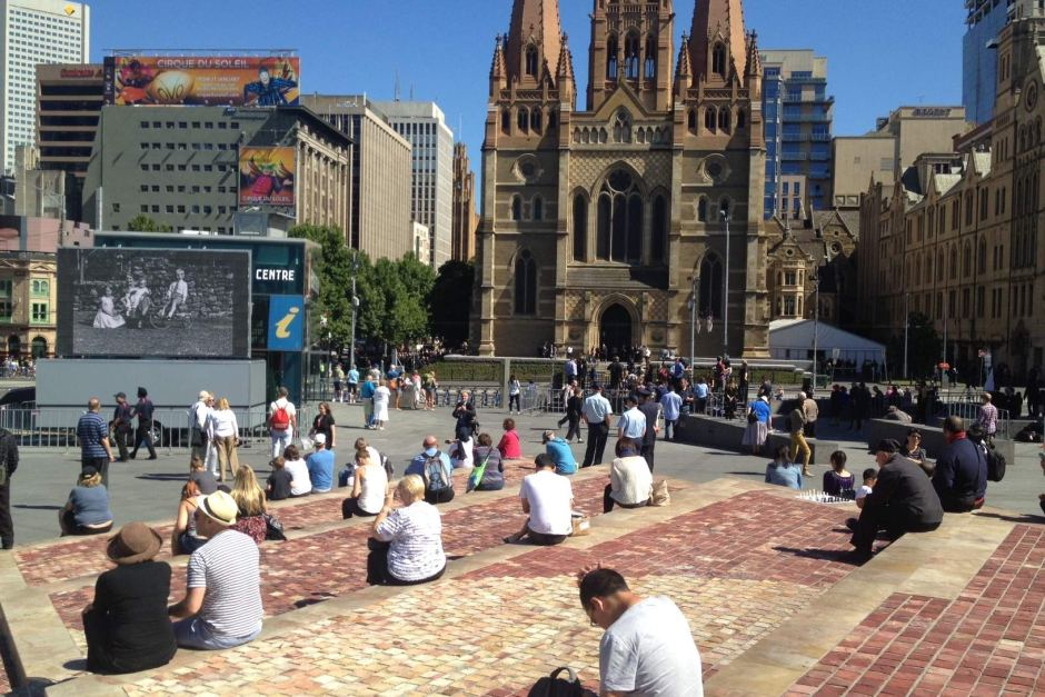 People gathered in front of a screen in Federation Square.